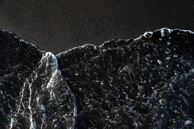Spiaggia con sabbia nera vulcanica e schiuma di onde sulla costa di bali