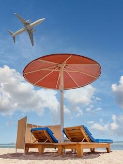 Spiaggia con ombrellone e lettini in riva al mare con aereo in volo nel cielo. concetto di vacanze estive.