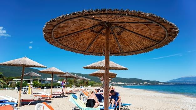 Spiaggia con ombrelloni, lettini e persone a riposo, olympiada, grecia