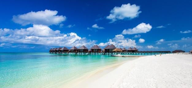 Spiaggia con sabbia bianca, acqua dell'oceano turchese e cielo blu con nuvole in una giornata di sole.