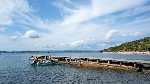 Spiaggiata in metallo motorizzata barca colorata su un molo sul mare egeo costa, colline e una città di ouranoupolis, grecia