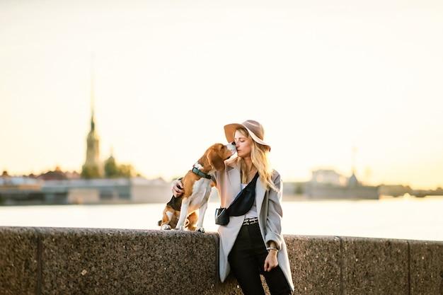 Cane beagle con contenuto giovane donna in abbigliamento casual con cappello