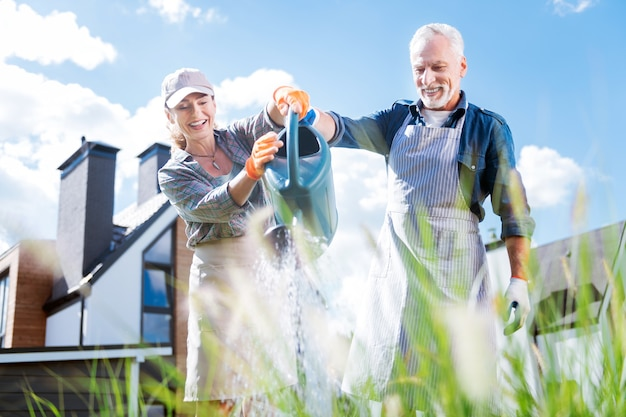 Coppia raggiante. trasmissione via ir di coppia di innamorati che tiene grande irrigatore da giardino mentre innaffia le piante nel letto da giardino insieme