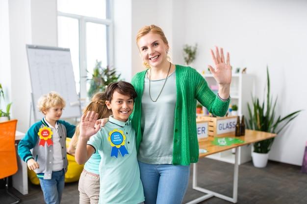 Insegnante e scolaro raggianti si sentono felici dopo la campagna ecologica e la raccolta differenziata