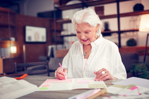 Donna raggiante. una donna dai capelli grigi raggiante si sente allegra mentre si gode il tempo libero a casa