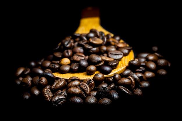 Caffè in grani su sfondo nero.