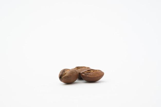 Chicco di caffè in sfondo bianco isolato. i chicchi di caffè a tostatura media sono di colore marrone chiaro su sfondo bianco.