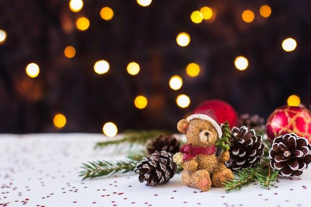 Orso e giocattoli di natale e pigne si trovano su uno sfondo bianco bokeh