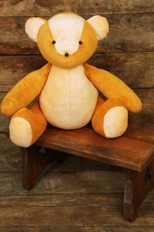 Giocattolo dell'orso sulla panca sul tavolo di legno