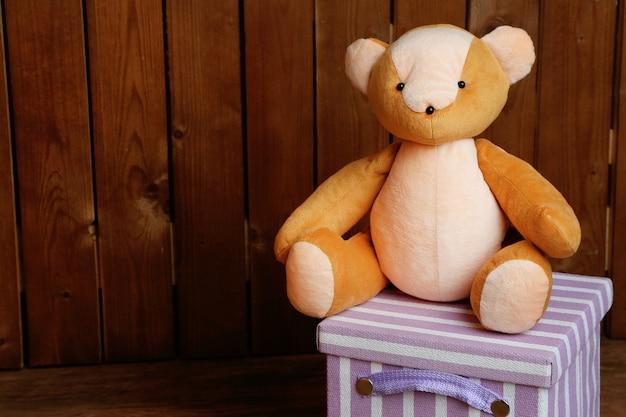 Giocattolo dell'orso sulla scatola su una superficie di legno
