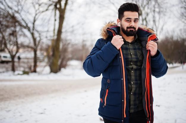 Barba uomo indiano indossare giacca in una fredda giornata invernale. auricolari mobili nelle orecchie.