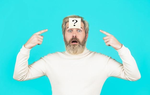 Punto interrogativo dell'uomo della barba in testa, problemi della soluzione uomo di pensiero con punto interrogativo su sfondo blu. uomo con punto interrogativo sulla fronte che guarda in alto. note di carta con punti interrogativi.