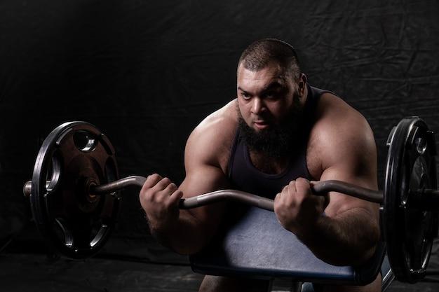 Il bodybuilder arabo barbuto lavora con le braccia sollevando un bilanciere su una panchina scott