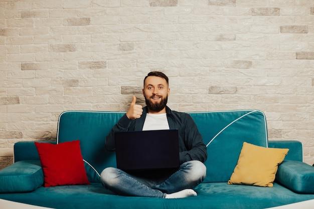 Ragazzo sorridente attraente barbuto sta usando al suo laptop, seduto a casa sull'accogliente divano di casa