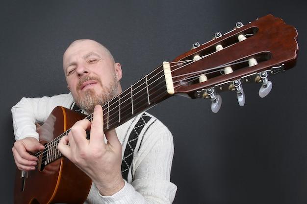 L'uomo calvo barbuto suona la chitarra classica