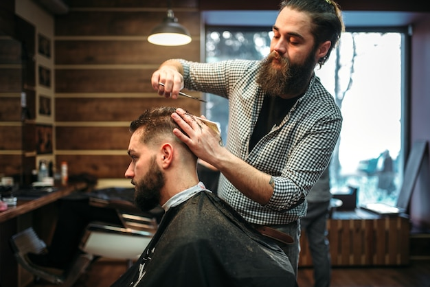Barbiere barbuto taglio acconciatura maschile client con le forbici. uomo in mantello nero salone dal barbiere