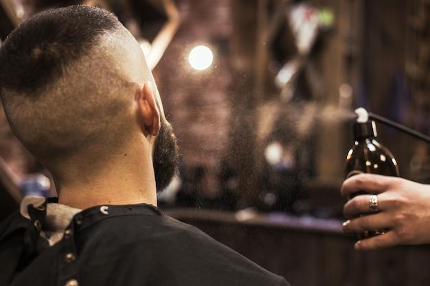 Il barbiere barbuto schizza sulla pelle del cliente dopo aver tagliato da una bomboletta spray