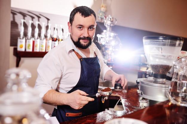 Barista barbuto che produce caffè
