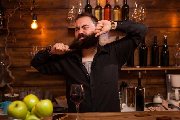 Barman barbuto che si diverte con la barba dietro il bancone di un pub vintage