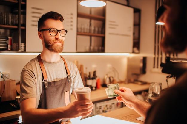Barman barbuto che indossa occhiali in piedi dietro il bancone del bar e con in mano una tazza di caffè che ha fatto per il cliente. il barista sembra serio. sembra che non abbia un umore.