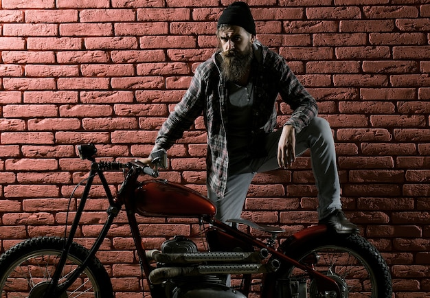 Uomo motociclista barbuto in moto