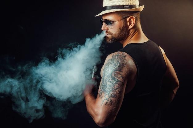 Uomo brutale barbuto con cappello e occhiali da sole che fuma una sigaretta a vapore come alternativa al tabacco sul nero