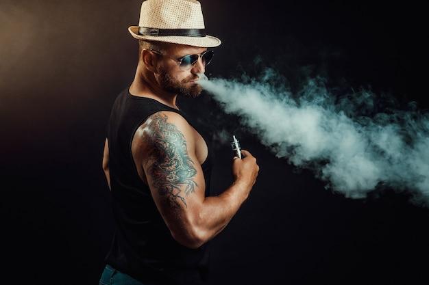 Maschio brutale barbuto con cappello e occhiali da sole che fuma una sigaretta di vapore come alternativa allo studio del tabacco girato in nero