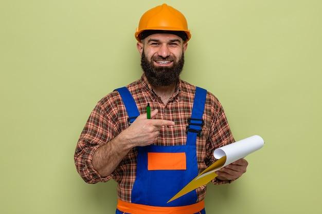Uomo barbuto costruttore in uniforme da costruzione e casco di sicurezza che tiene appunti che puntano con il dito indice sorridendo allegramente in piedi su sfondo verde