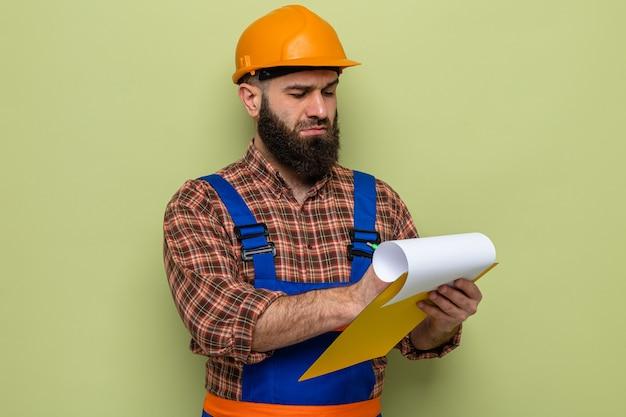Uomo barbuto costruttore in uniforme da costruzione e casco di sicurezza che tiene appunti con pagine bianche che prendono appunti guardando fiduciosi in piedi su sfondo verde