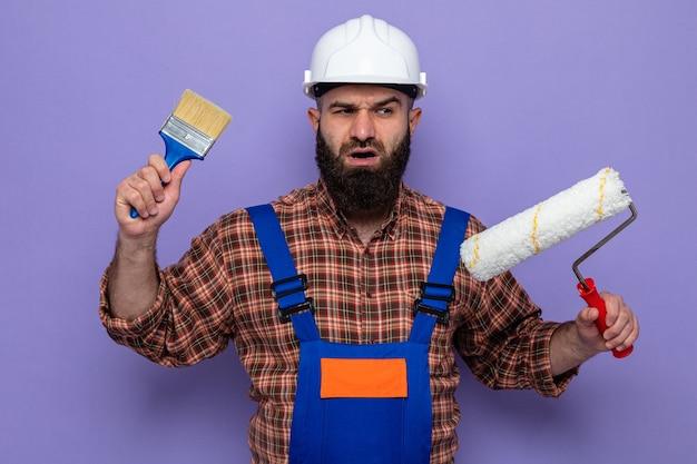 Uomo barbuto costruttore in uniforme da costruzione e casco di sicurezza che tiene rullo di vernice e pennello che sembra confuso avendo dubbi guardando in piedi su sfondo viola