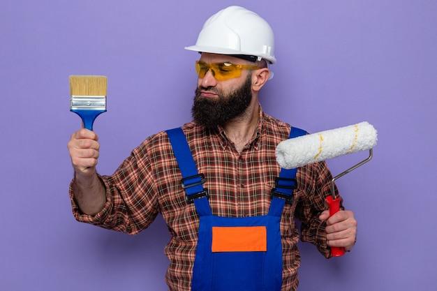 Uomo barbuto costruttore in uniforme da costruzione e casco di sicurezza che tiene rullo di vernice e pennello che sembra confuso avendo dubbi in piedi su sfondo viola