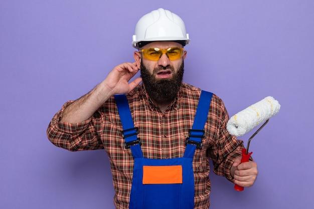 Uomo barbuto costruttore in uniforme da costruzione e casco di sicurezza che tiene il rullo di vernice guardando la telecamera confuso cercando di sentire tenendo la mano vicino al suo orecchio in piedi su sfondo viola