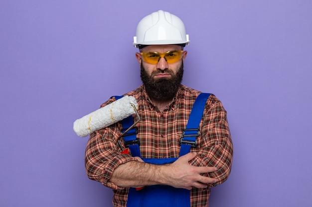 Uomo barbuto costruttore in uniforme da costruzione e casco di sicurezza che tiene rullo di vernice guardando la telecamera con una faccia seria con le braccia incrociate in piedi su sfondo viola purple