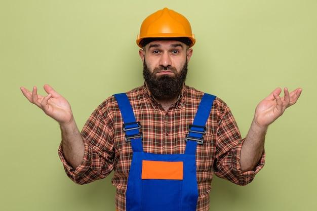 Uomo barbuto costruttore in uniforme da costruzione e casco di sicurezza che guarda la telecamera confuso alzando le spalle senza risposta in piedi su sfondo verde