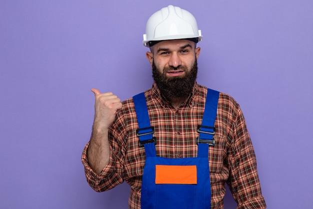 Uomo barbuto costruttore in uniforme da costruzione e casco di sicurezza che sembra sorridente fiducioso che punta con il pollice di lato