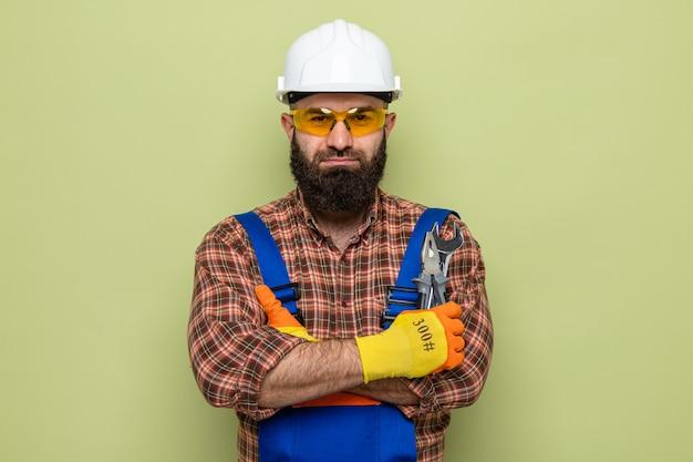 Uomo barbuto costruttore in uniforme da costruzione e casco di sicurezza che indossa guanti di gomma che tengono la chiave inglese guardando la telecamera con espressione seria e sicura con le braccia incrociate in piedi su sfondo verde