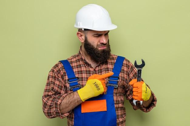 Uomo barbuto costruttore in uniforme da costruzione e casco di sicurezza che indossa guanti di gomma tenendo la chiave inglese puntata con il dito indice su di esso essendo incuriosito in piedi su sfondo verde