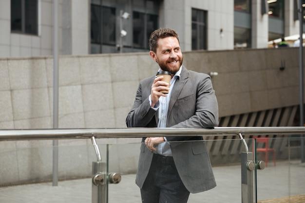 Uomo d'affari barbuto in abito grigio che guarda da parte con un sorriso, mentre in piedi e beve caffè da asporto davanti al moderno centro business