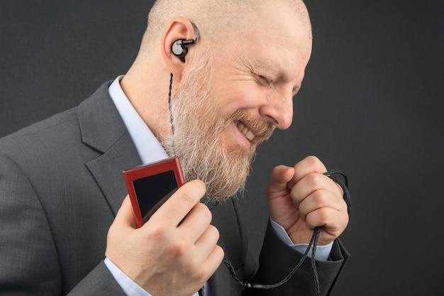 L'uomo d'affari barbuto ama ascoltare la sua musica preferita a casa con un lettore audio in piccole cuffie. audiofilo e amante della musica. musica e suono hi-fi.