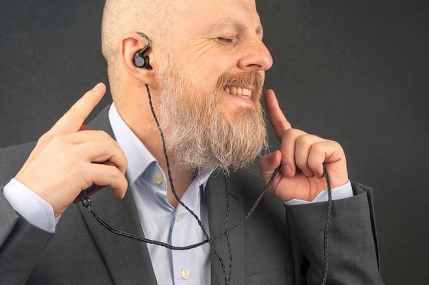 Uomo d'affari barbuto ama ascoltare la sua musica preferita a casa con un lettore audio in piccole cuffie