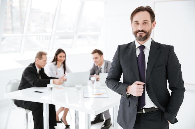 Uomo d'affari barbuto in ufficio con i colleghi al tavolo