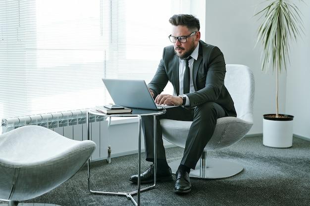 Barbuto uomo d'affari in abito elegante seduto in poltrona davanti al computer portatile in ufficio e l'invio di posta elettronica a un collega o un partner commerciale