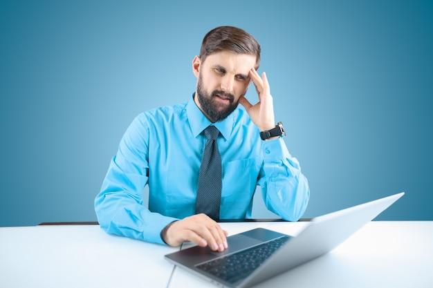 Un uomo d'affari con la barba davanti a un computer portatile ha appoggiato la mano alla testa ha forti mal di testa, un uomo seduto in ufficio al computer ha mal di testa