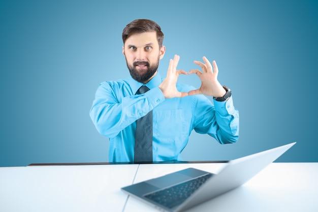 Un uomo d'affari barbuto davanti a un laptop mostra il suo cuore con le dita, un uomo in camicia e cravatta mostra le emozioni dell'amore