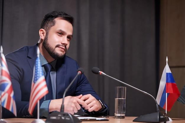 Uomo d'affari barbuto seduto in una sala riunioni con microfono, dirigente di successo e fiducioso che parla con il team, lavorando durante la riunione. concetto di persone di affari e di successo