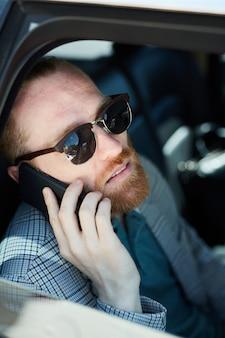 Uomo d'affari barbuto che parla sul telefono dentro dell'automobile
