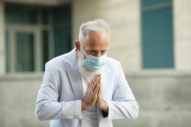 Uomo d'affari barbuto che indossa la maschera per il viso e saluto con namaste per prevenire la diffusione del virus