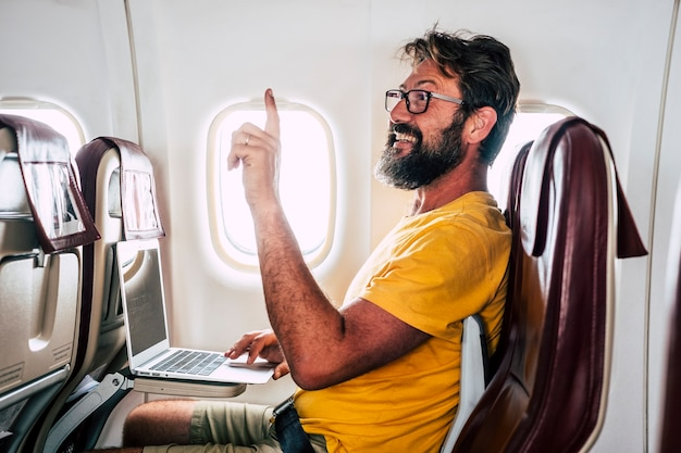 L'uomo adulto caucasico barbuto si siede all'interno del volo dell'aereo chiedendo aiuto per l'hostess