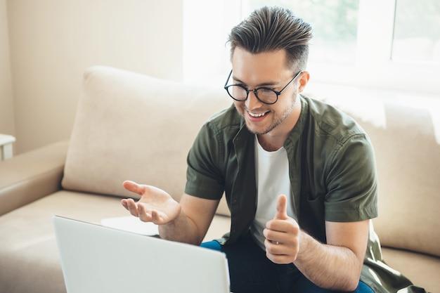 Ragazzo caucasico barbuto con gli occhiali che hanno una riunione in linea al computer portatile a casa che si siede sul divano