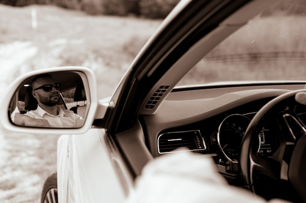 Uomo d'affari caucasico barbuto che guarda l'obbiettivo attraverso lo specchietto retrovisore testa e spalle